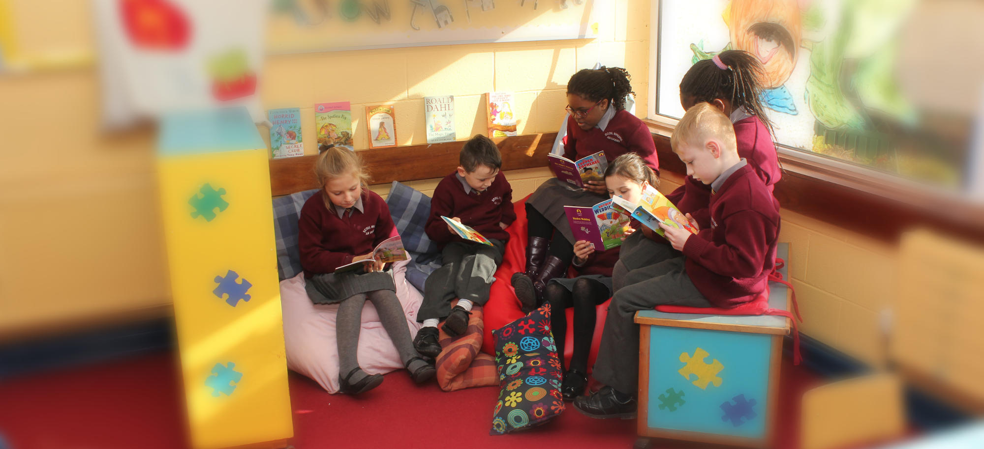 Children reading books in a cosy corner of one of the classrooms.