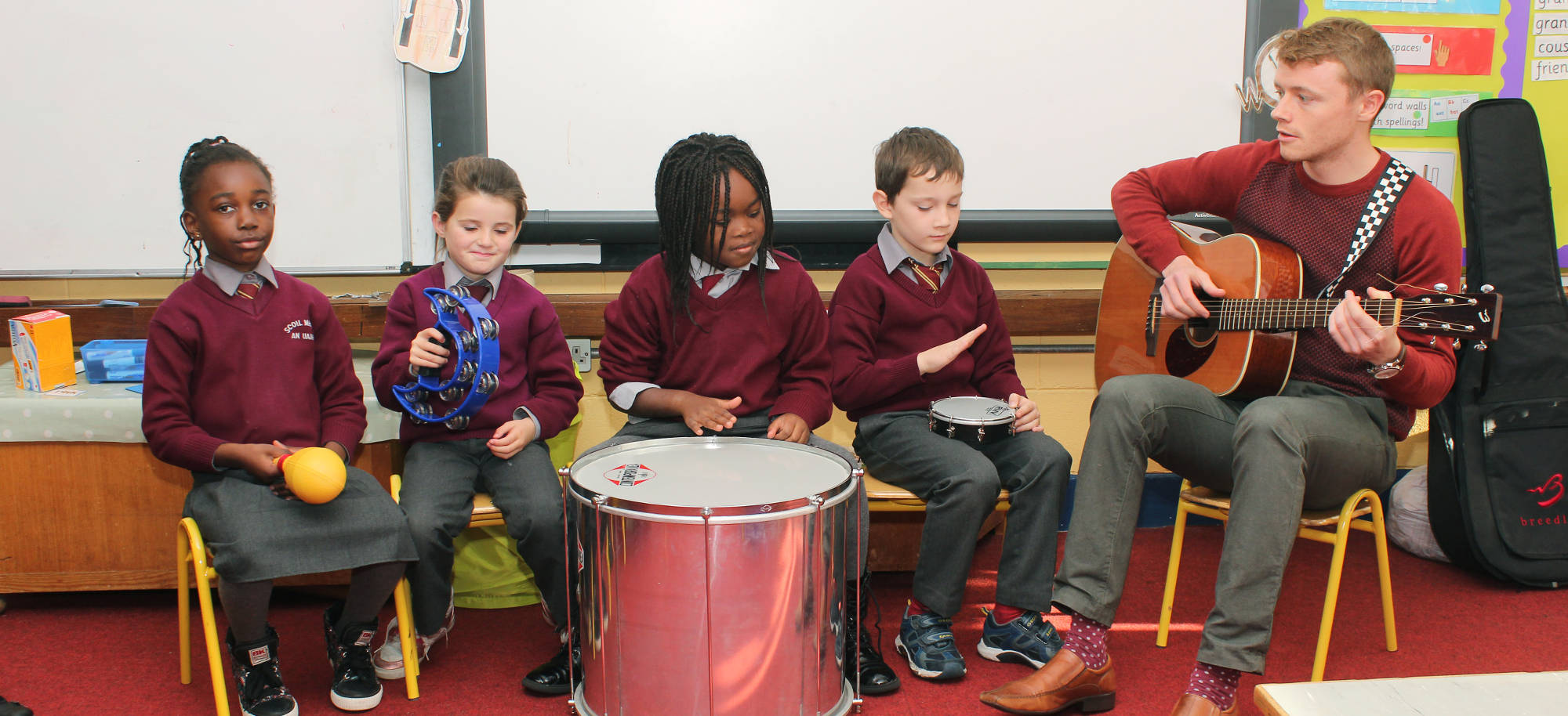 Pupils holding various musical instruments enjoying music class with a teacher playing guitar.