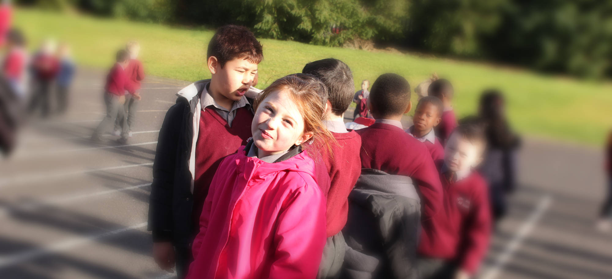 A pupil looking straight into camera with other children playing in the courtyard background.